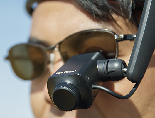 Drone pilot wearing an AiRScouter WD-300C headset over sunglasses