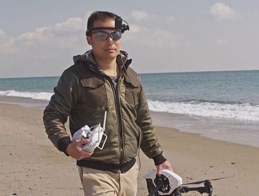 Drone operator walking on beach wearing an AiRScouter WD-300C headset