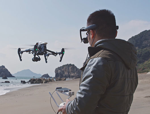 Drone operator flying a over a beach while wearing an AiRScouter WD-300C