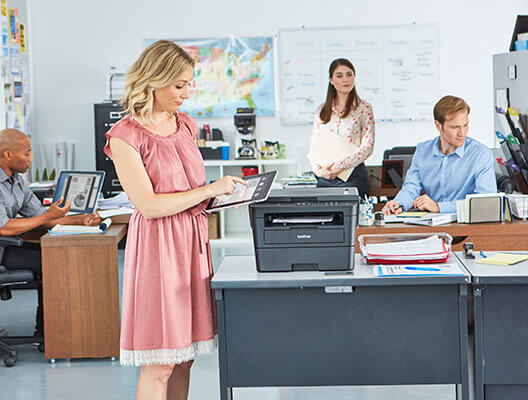 Two Men and Women using brother printer in office
