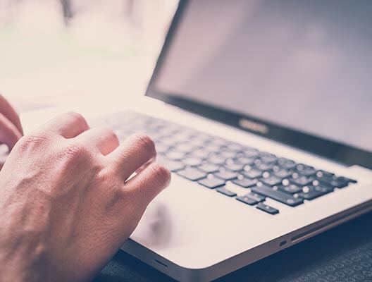 Close up of man typing on a laptop