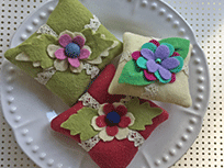 Three red, green, and beige pincushions on a white ceramic plate