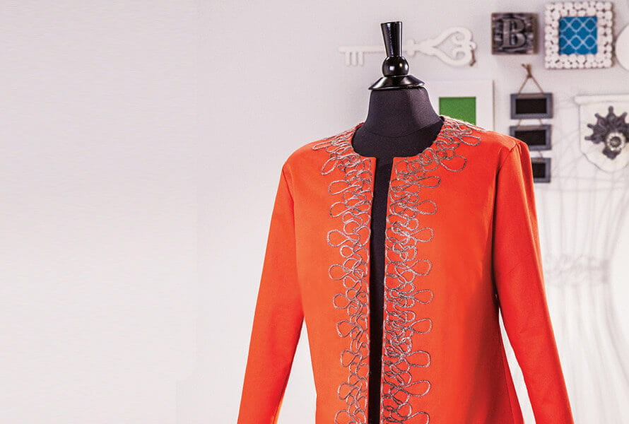 Embellished orange shirt displayed on mannequin