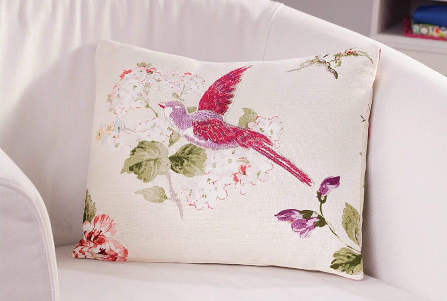 White arm pillow with pink bird and floral patterns