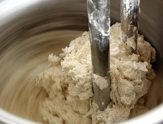 Large mixing vat turning dough with motion blur