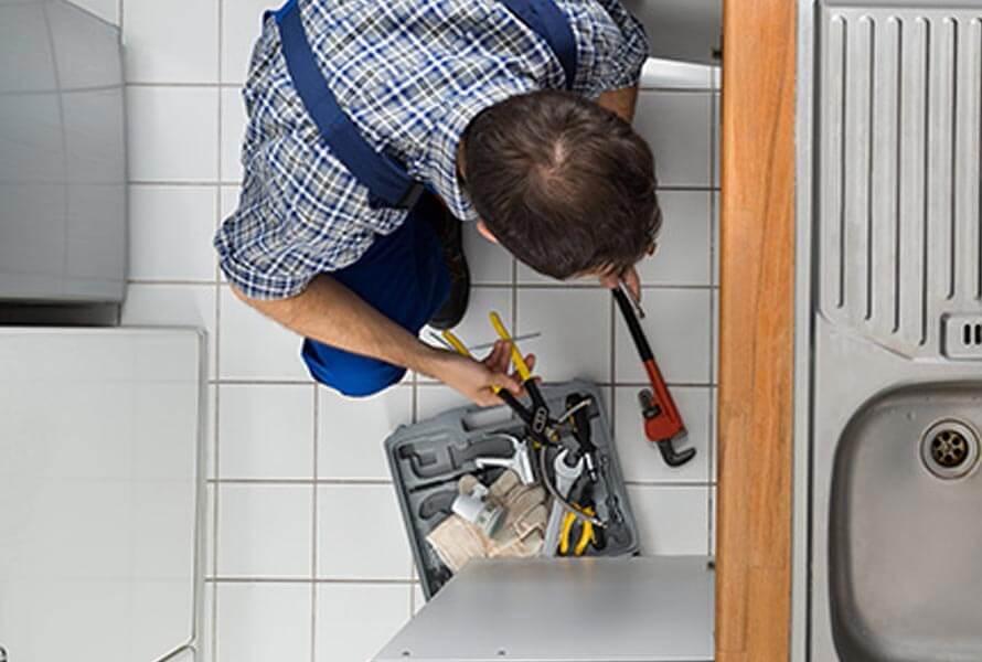 Overview of man performing plumbing work