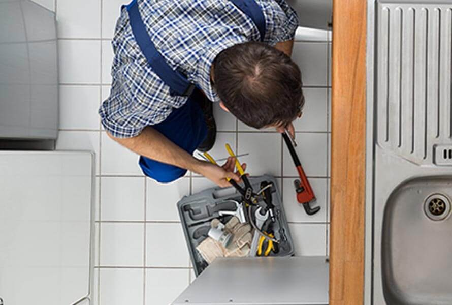 Overview of man performing plumbing work