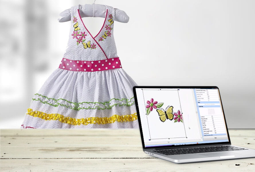 Monogrammed dress next to laptop showing the design template