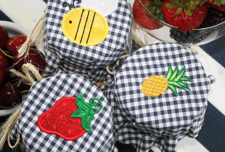 Canning jars wrapped with embroidered checkered pattern