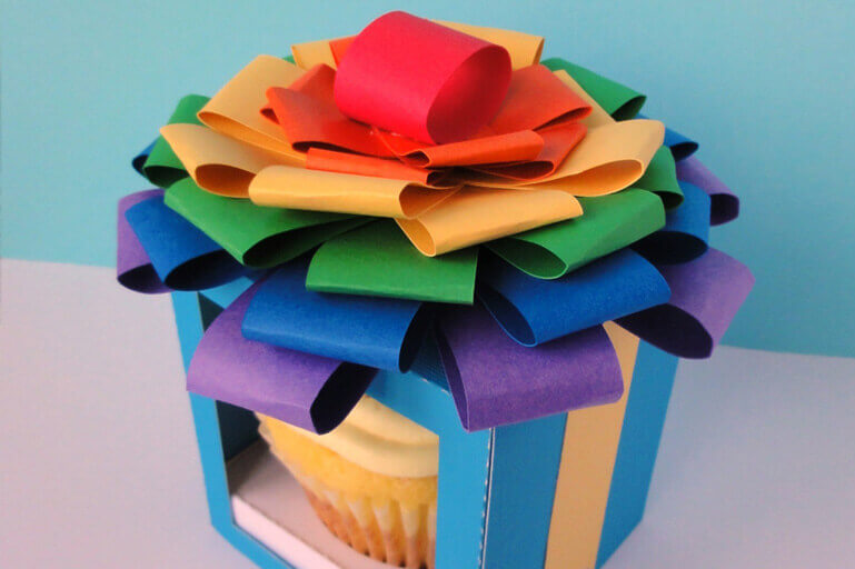 Cupcake in box with clear front, topped with multi-color ribbons to form a bow