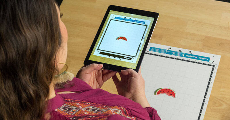 Woman holding tablet using ScanNCutCanvas cloud app