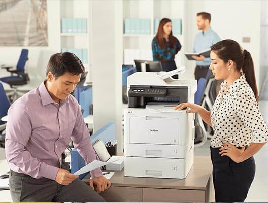 Man and woman in office with Brother printer