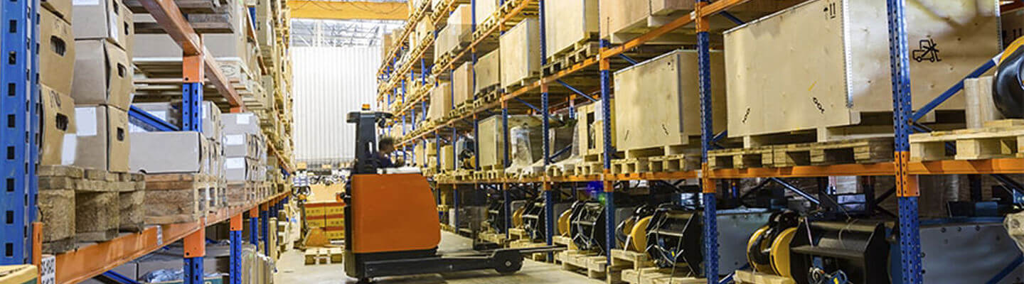 Forklift operator in warehouse aisle