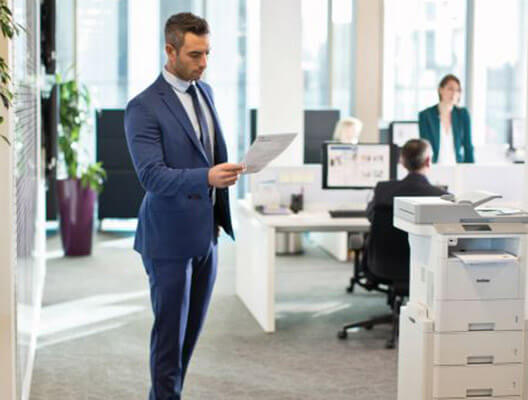 Man in blue suit examines printed paper