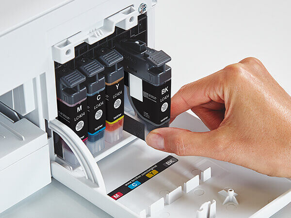 Person inserting new Brother Genuine LC404 ink cartridge into printer