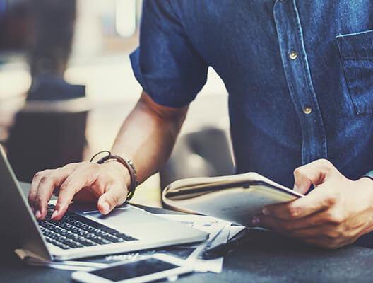 Man in denim shirt using a laptop