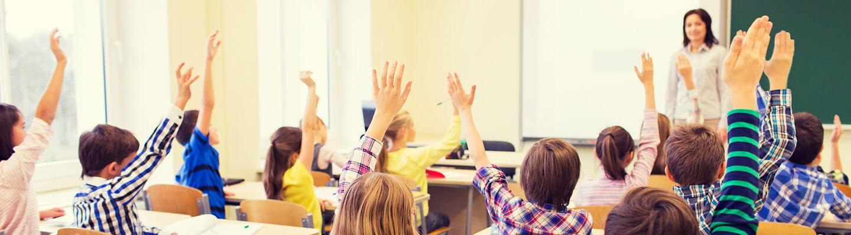 Many children in class raising their hands