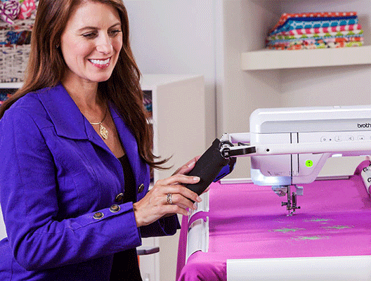 Image of a woman using the ergonomic handles on THE Dream Fabric Frame while quilting