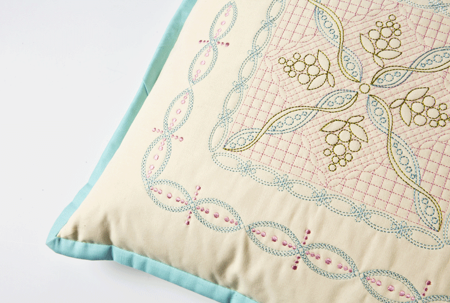 Beige pillow with blue welt and custom embroidered design