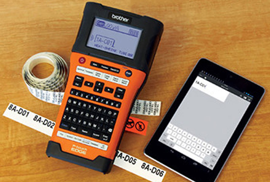 Orange Brother P-touch with labels and tablet on desk
